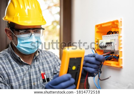 Electrician at work on an electrical panel protected by helmet, safety goggles and gloves; wear the surgical mask to prevent the spread of Coronavirus. Construction industry. Covid-19 Prevention.