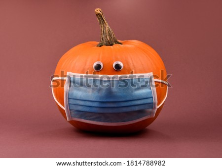 Orange pumpkin with protective mask stock images. Funny halloween pumpkin with coronavirus mask isolated on a brown background photo images. Pumpkin wearing medical mask on face to prevent flu image
