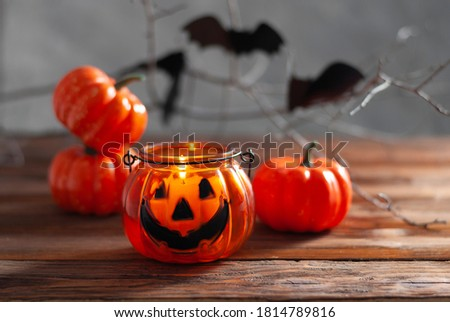 Halloween pumpkins on the wooden table with black wall and garland yellow lights. Happy halloween card beautiful picture