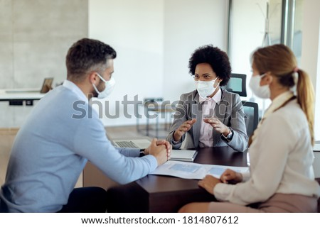 Black real estate agent and a couple wearing protective face masks while communicating during the meeting in the office.  #1814807612