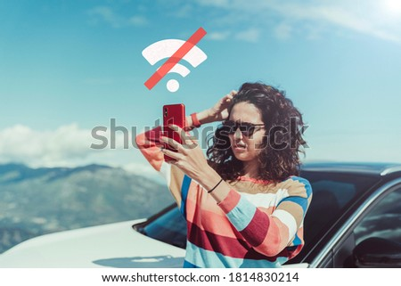 Worried woman looking for signal after car breakdown. She is holding red mobile with no signal illustration. She is wearing colorful scratch jersey. There is mountain landscape with blue sky on back Royalty-Free Stock Photo #1814830214