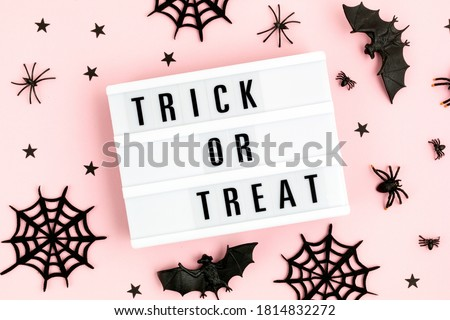 Halloween flat lay of lightbox with Trick or treat text and decoration over pink background. Holiday greeting card, party flyer, invitation concept