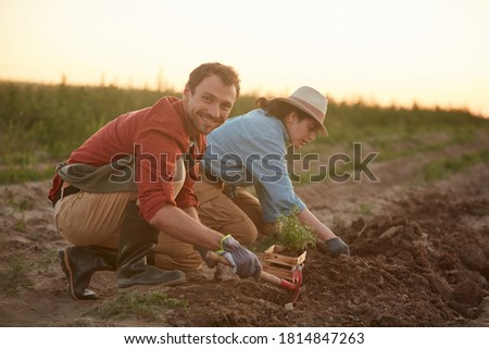 Full length portrait of two people working in field at vegetable plantation, focus on young man planting saplings in foreground and smiling at camera, copy space Royalty-Free Stock Photo #1814847263