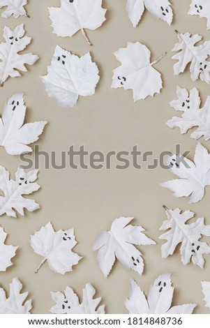 Flat lay Halloween background made with autumn leaves painted in white like ghosts. Minimal season holiday concept