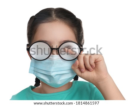 Little girl wiping foggy glasses caused by wearing medical face mask on white background. Protective measure during coronavirus pandemic Royalty-Free Stock Photo #1814861597