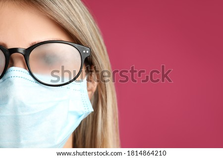 Woman with foggy glasses caused by wearing disposable mask on pink background, space for text. Protective measure during coronavirus pandemic Royalty-Free Stock Photo #1814864210