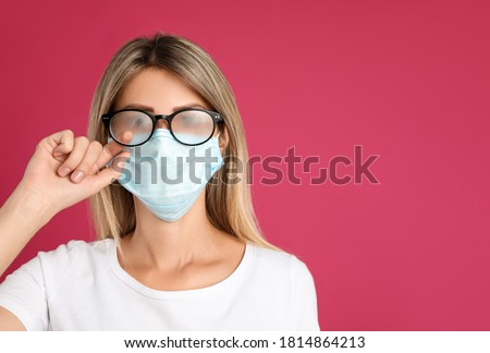 Woman wiping foggy glasses caused by wearing disposable mask on pink background, space for text. Protective measure during coronavirus pandemic Royalty-Free Stock Photo #1814864213