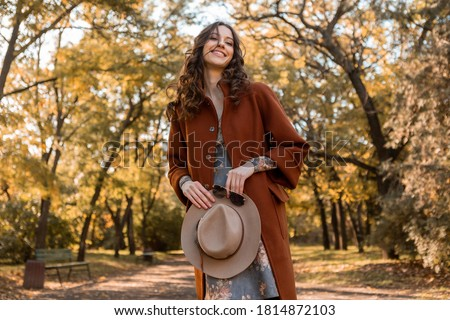 close-up hands details of attractive stylish woman holding hat and sunglasses walking in park dressed in warm coat autumn trendy street fashion style accessories Royalty-Free Stock Photo #1814872103