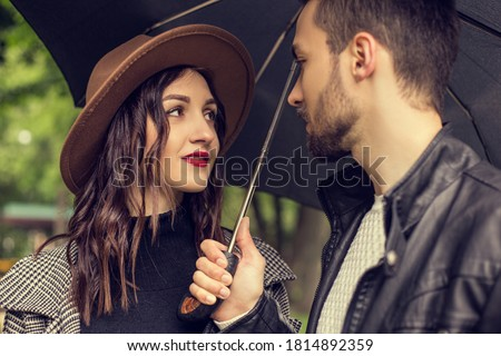 Portrait of young loving couple walking in the city park and use umbrella to shelter the rain. Heterosexual lovers have a date, spending time together in cloudy rainy day, showing emotions. #1814892359