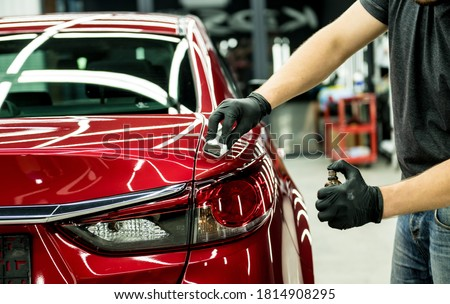 Car service worker applying nano coating on a car detail. Royalty-Free Stock Photo #1814908295