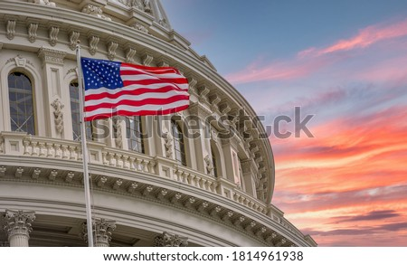 View of the United States Capitol Rotunda Dome in Washington DC with the Star Spangled American Flag against colorful dramatic sunset sky background Royalty-Free Stock Photo #1814961938