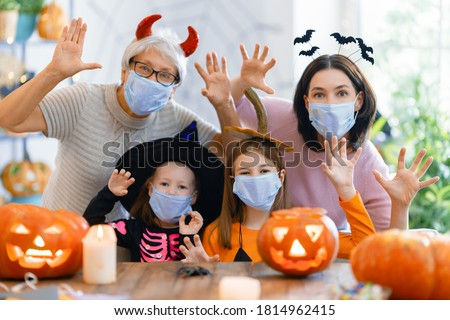 Happy family celebrating Halloween. Grandmother, mother and children wearing face masks protecting from COVID-19. Royalty-Free Stock Photo #1814962415