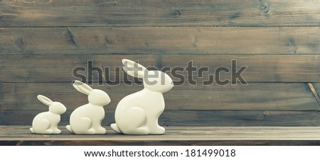easter bunnies over rustic wooden background. retro style toned picture