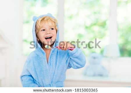 Child brushing teeth. Kids tooth brush and paste. Little baby boy in blue bath robe or towel brushing his teeth in white bathroom with window on sunny morning. Dental hygiene and heath for children. #1815003365