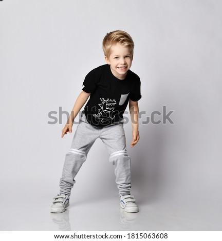 Playful frolic blond kid boy in sunglasses, black t-shirt with dinosaur print and gray pants stands leaning forwards going to run out playing catch-up over gray background Royalty-Free Stock Photo #1815063608