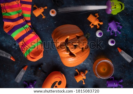 Halloween picture with two smiling pumpkins, party stripped socks, artificial eyes and other halloween objects. Halloween pumpkins isolated on dark background. Spooky halloween.