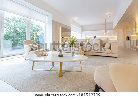 trendy modern interior design of a large studio in white and beige colors with large floor-to-ceiling windows. area of white kitchen with an island and a recreation area #1815127091