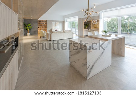 trendy modern interior design of a large studio in white and beige colors with large floor-to-ceiling windows. area of ​​white kitchen with an island and a recreation area #1815127133