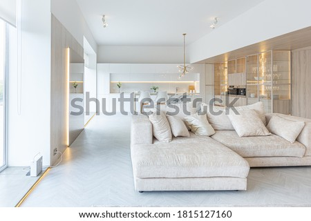 trendy modern interior design of a large studio in white and beige colors with large floor-to-ceiling windows. area of white kitchen with an island and a recreation area Royalty-Free Stock Photo #1815127160