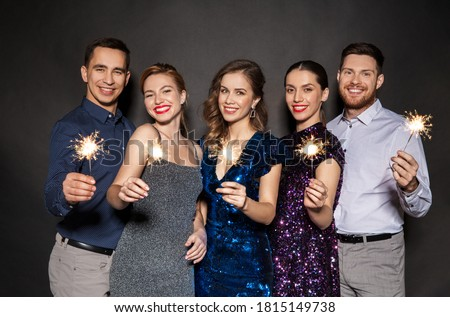 celebration, people and holiday style concept - happy friends in party clothes with sparklers over black background #1815149738
