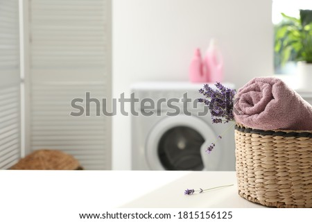 Wicker basket with rolled clean towel and lavender flowers on white table indoors. Space for text #1815156125