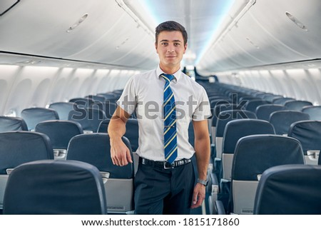 Close up portrait of handsome confident steward posing at the photo camera near the cozy chair of passenger aircraft Royalty-Free Stock Photo #1815171860