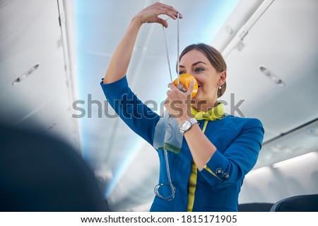 Portrait of smiling cheerful flight attendant demonstrating how grasping mask over nose and mouth while slip elastic band over head Royalty-Free Stock Photo #1815171905