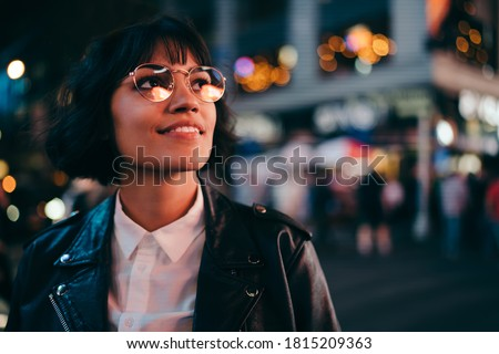 Carefree brunette young woman with short haircut in stylish eyewear for eyes protection fascinated with New York urbanity in Manhattan,youthful female in leather jacket enjoying metropolitan nightlife Royalty-Free Stock Photo #1815209363