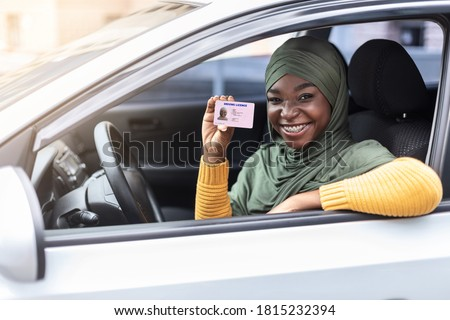 Cheerful happy black muslim woman in hijab sitting in her car and showing new driver license, celebrating driving school finish, passed exam, bought car, sitting inside of vehicle, looking from window #1815232394