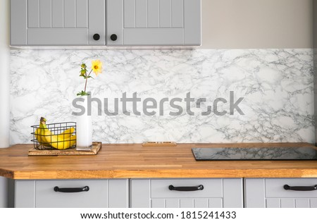 Modern minimal gray color kitchen with self adhesive fake marble imitation tape on wall, solid natural wood countertop with built in small stove. Royalty-Free Stock Photo #1815241433