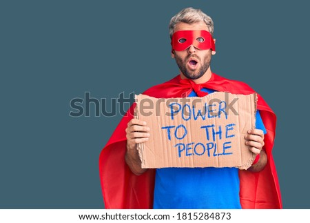 Young blond man wearing super hero custome holding power to the people cardboard banner scared and amazed with open mouth for surprise, disbelief face