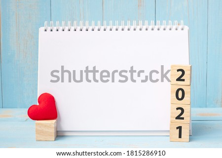 blank notebook and 2021 cubes with red heart shape decoration on blue wooden table background. New Year NewYou, Goal, Resolution, health, Love and Happy Valentine's day concept #1815286910