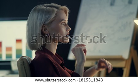 Thoughtful business woman analyzing income charts on computer in night office. Pensive woman working late with financial reports in dark office. Closeup woman having overtime work in evening office Royalty-Free Stock Photo #1815311843