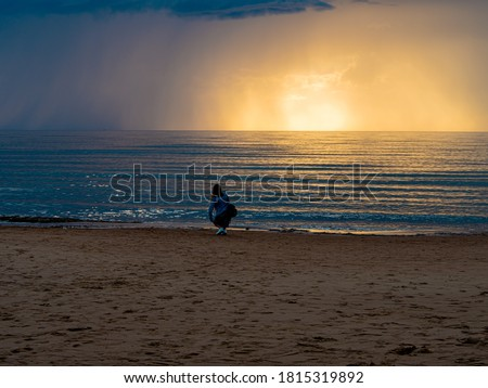 beautiful alone girl on the beach. Girl looking at stormy sea amd taking a picture with smarphone. The spectacular Storm with rain Is Coming in Estonia. Baltic sea