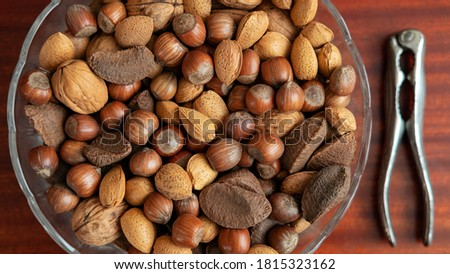 Assortment of whole nuts, walnuts, almonds, hazelnuts and Brazil nuts in a bowl with a nut cracker on a side, nutritious snack cracked and eaten in autumn or winter months as a special holidays treat. Royalty-Free Stock Photo #1815323162