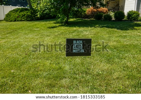 Black sign with blue writing on a green grass lawn that says black lives matter