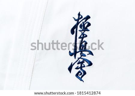 """Kyokushinkai karate symbol on cotton background. """"Kyokushin"""" is a style of stand-up, full contact karate and is Japanese for """"the ultimate truth"""". Royalty-Free Stock Photo #1815412874"""