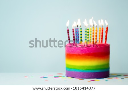 Rainbow colored birthday cake with brightly colored birthday candles Royalty-Free Stock Photo #1815414077