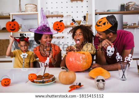 Happy family mother father and children prepare for Halloween. They are carving pumpkin.