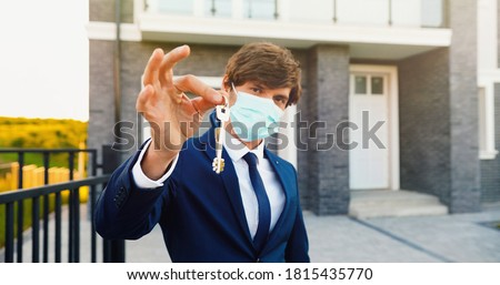 Portrait of young handsome man real-estate agent standing near new house and showing key. Male in medical mask holding house key. Selective focus on hands, close up. #1815435770