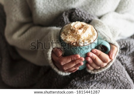 Woman with blanket warming her hands in mug of hot drink with whipped cream Royalty-Free Stock Photo #1815441287