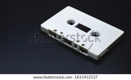Old audio cassettes on dark wooden background.