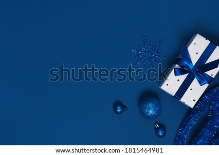 Present box wrapped with a ribbon, decorative balls and snowflake on colorful paper background. Christmas gift. Holiday concept. Image is with copy space. Flat lay. Top view #1815464981