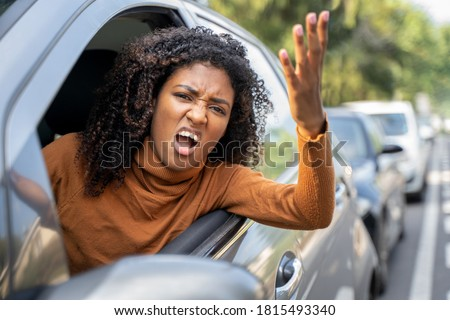 Aggressive woman driving car shouting at someone Royalty-Free Stock Photo #1815493340