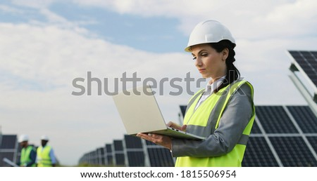 Beautiful business lady standing among field of solar panels in special uniform. Female engineer uses laptop to work outside. Royalty-Free Stock Photo #1815506954