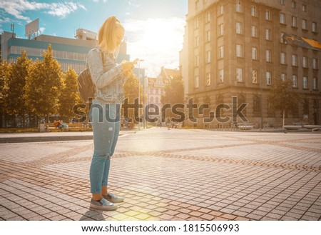 Selfie woman. Happy young girl with phone smile, typing texting and taking selfie in summer sunshine urban city. Pretty female taking fun self portrait photo. Vanity, social network concept.