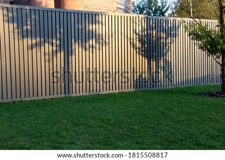 Shadows of trees on the fence of the park at sunset in September and the shadows of two people - one takes pictures of the other sitting on the lawn