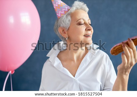 Close up image of ecstatic happy retired lady in stylish white shirt and cone hat dancing to music at birthday party, holding pink helium balloon. Festivity, celebration, fun and entertainment concept