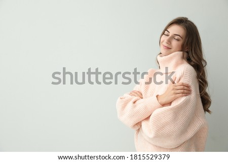 Beautiful young woman wearing warm pink sweater on light background. Space for text Royalty-Free Stock Photo #1815529379