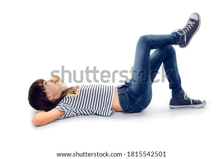 10 year old girl look up while lie on ground with legs crossed Royalty-Free Stock Photo #1815542501